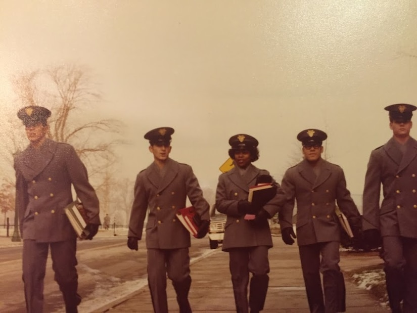 A group of 5 soldiers holding books walk together.