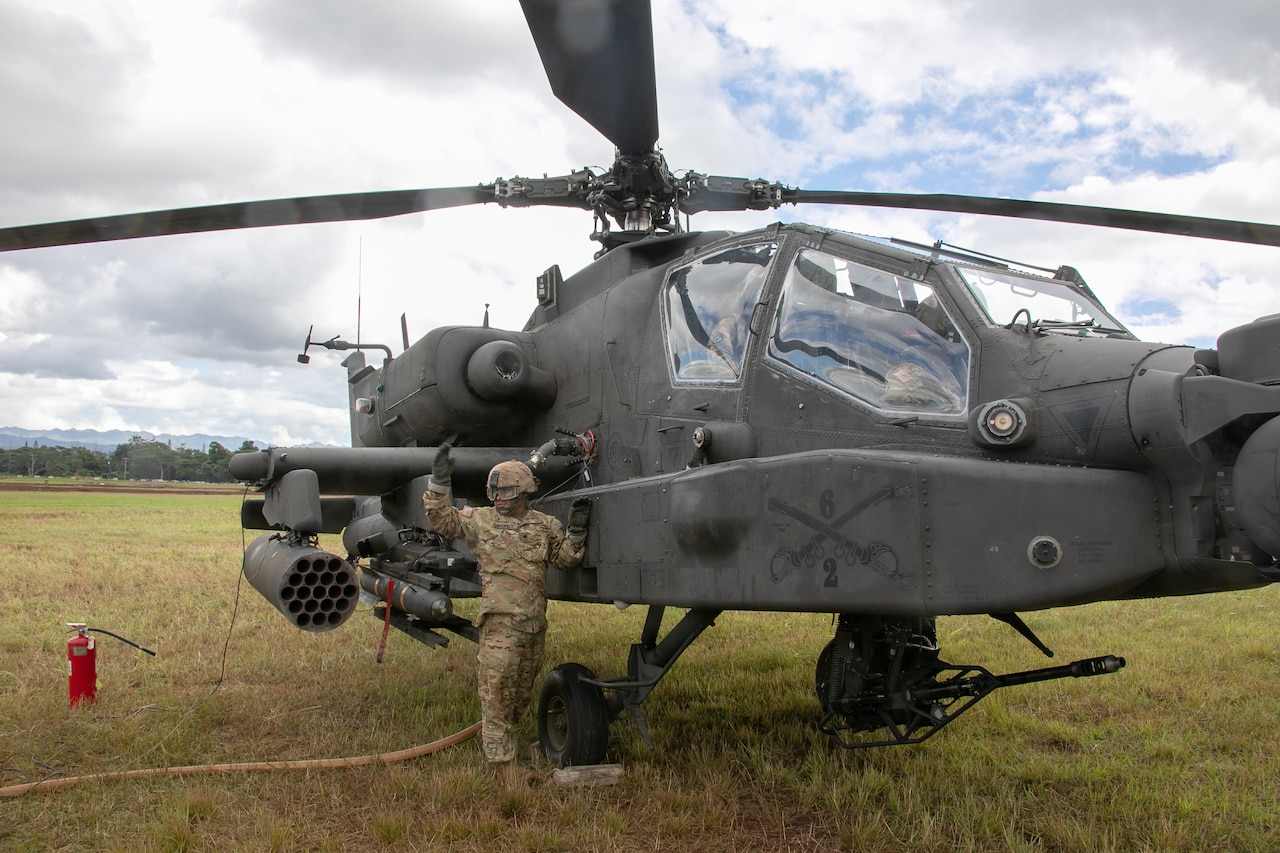 A soldier refuels a helicopter.
