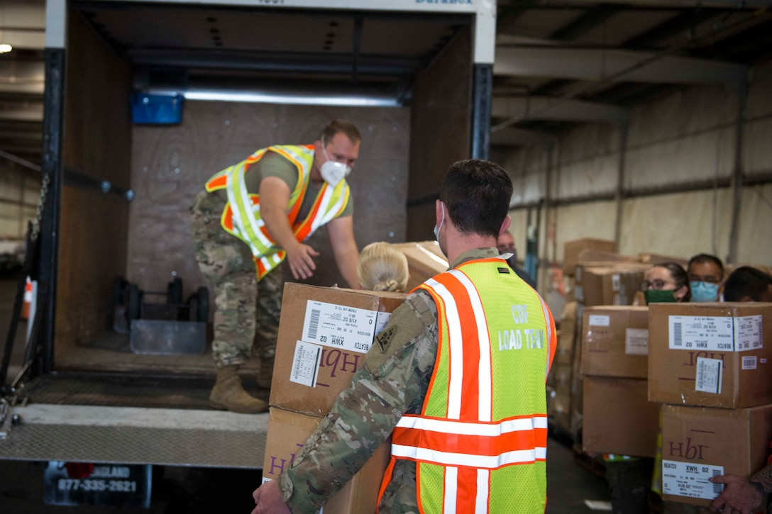Soldiers and airmen wearing protective equipment load boxes into a vehicle.