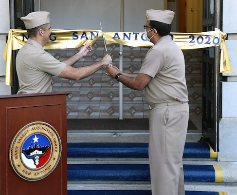 Cmdr. Nicholas Gamiz (left), commanding officer of Navy Talent Acquisition Group San Antonio, and executive officer Cmdr. Michael Files cut the ceremonial ribbon which decommissioned Navy Recruiting District San Antonio and established NTAG San Antonio at NTAG headquarters.
