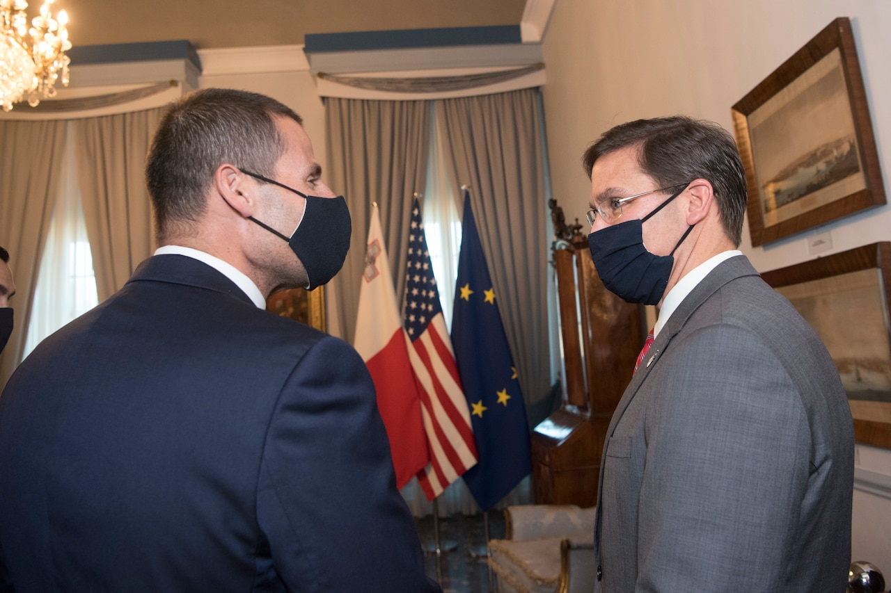 Two men, wearing masks, meet. The flags of Malta, the U.S. and the European Union are in the background.