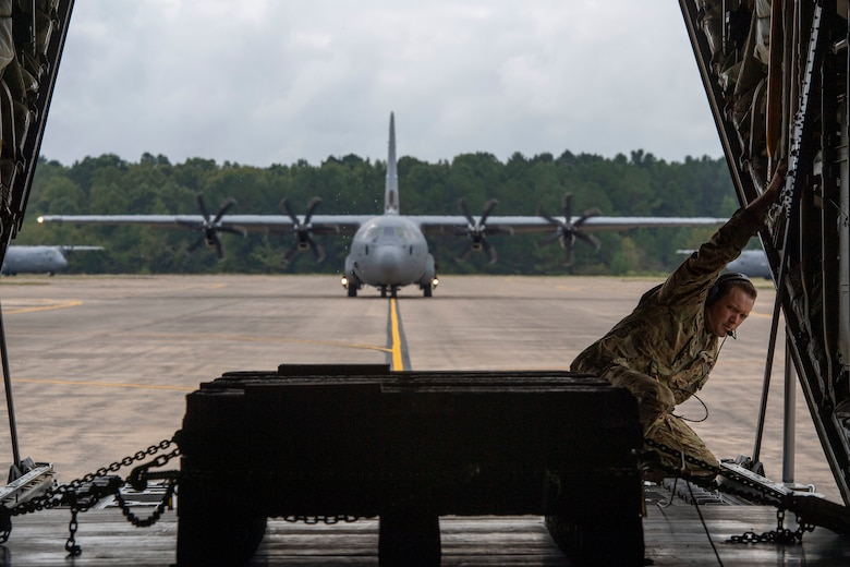 A loadmaster looks out the back of a C-130J.