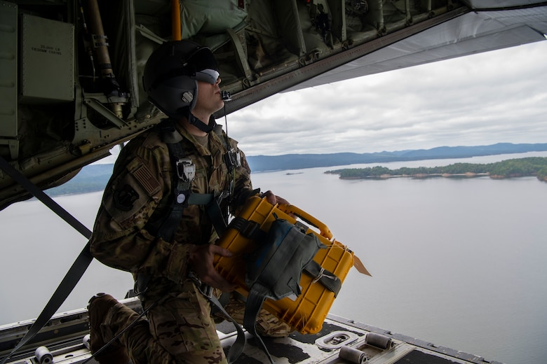 A loadmaster prepares for an airdrop over a lake.