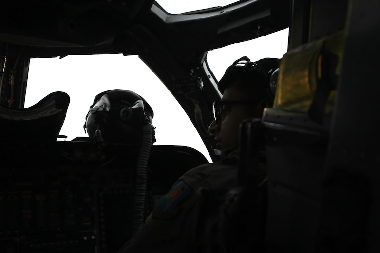 Photo of B-1 pilot performing pre-flight checks in cockpit.