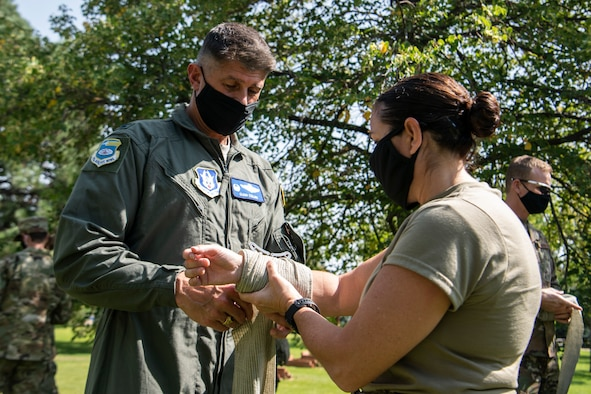 Col. Glen Collins, 932nd Airlift Wing commander, practices self-aid and buddy care on Chief Master Sgt. Barbara Gilmore, 932nd AW command chief, during Operation Centennial Summit, Peterson Air Force Base, Colorado, Sept. 15, 2020. Operation Centennial Summit gave members the opportunity to get hands-on training such as litter carry procedures, triage, self-aid and buddy care, respiratory distress and numerous lectures on other medical emergencies. The 932nd AW is a reserve unit at Scott Air Force Base, Illinois. (U.S. Air Force photo by Senior Airman Brooke Spenner)