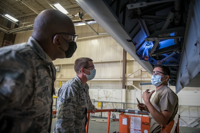 Tech. Sgt. Jesse Zambrano, 302nd Maintenance Squadron C-130 crew chief, right, discusses the process of installing major flight controls in a C-130 Hercules with C-40C crew chiefs, Senior Airman Landon Wineland, middle, and Senior Airman Earnest Carter, both from the 932nd Maintenance Group. (Master Sgt. Christopher Parr)
