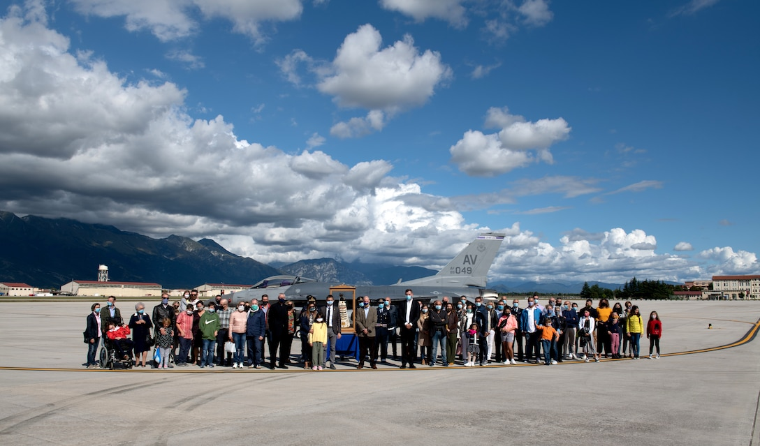 Attendees pose for a group photo with the Madonna Di Loreto statue at Aviano Air Base, Italy, Sept. 27, 2020. The statue is on a pilgrimage around Italy in celebration of the centenary of her proclamation as the Patroness of Aeronauts. (U.S. Air Force photo by Senior Airman Caleb House)
