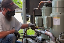Matt Greer, a member of U.S. Marine Corps Forces Command, Fleet Marine Force Atlantic, Facility Maintenance Team, brazes the pipes of the heating, ventilation, and air conditioning system (HVAC) May 13, 2020, at Hopkins Hall Gym, on Camp Elmore in Norfolk, Virginia.