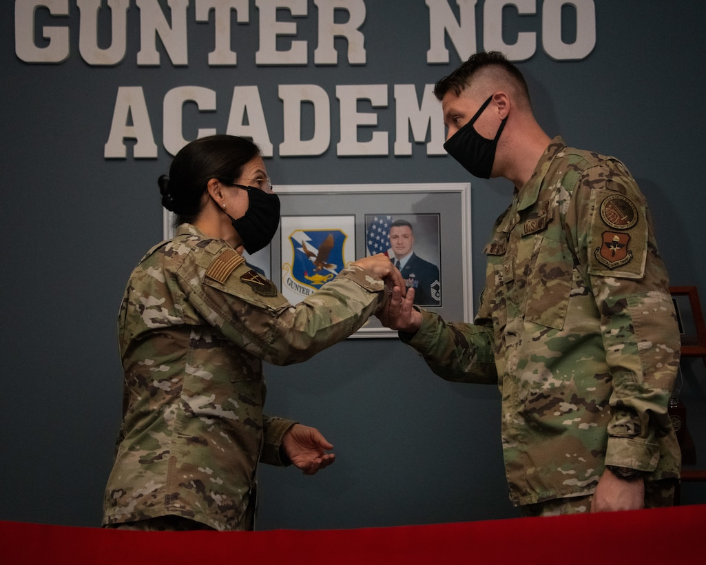 Col. Kathryn Brown, Thomas N. Barnes Center for Enlisted Education commander, presents a coin to Tech. Sgt. Jonathan Kertulis