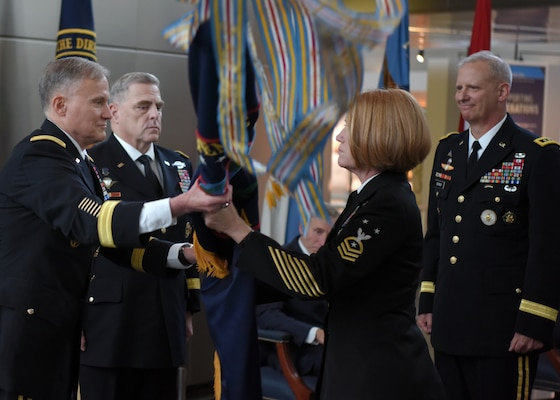 Former Defense Intelligence Agency Director Lt. Gen. Robert Ashley Jr (front left) hands the DIA flag to DIA Command Senior Enlisted Leader Command Master Chief Laura Nunley during the DIA Change of Directorship Ceremony. Chairman of the Joint Chiefs of Staff Gen. Mark Milley (back left) presided over the ceremony in which Lt. Gen. Scott Berrier (right) became the 22nd director of DIA.