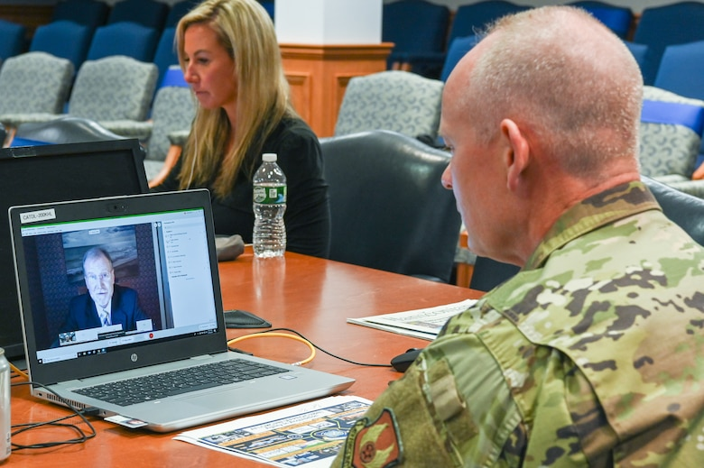 Maj. Gen. Michael Schmidt, right, program executive officer for Command, Control, Communications, Intelligence and Networks, speaks to Steve Wert, PEO for Digital, and other Hanscom Collaboration and Innovation Center symposium participants via Webex, while Caitlin Sullivan, with Gartner Air Force Programs, looks on, Sept. 30.