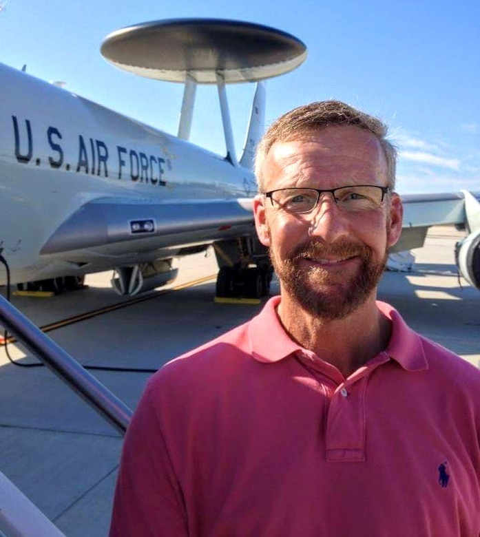 Steve Ober, Diversity and Inclusion manager at Hanscom Air Force Base, Mass., stands in front of an E-3 Airborne Early Warning and Control System aircraft at Pease Air Force Base, N.H., in 2016. As the installation D&I manager, Ober will facilitate events, training and resources to create a more inclusive Hanscom community. (Courtesy Photo)