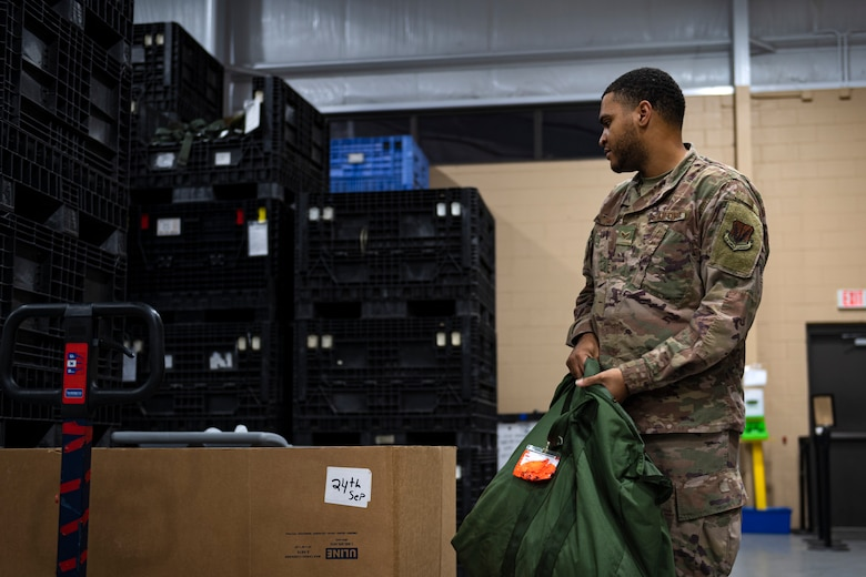 A photo of an Airman holding a bag of individual protective equipment