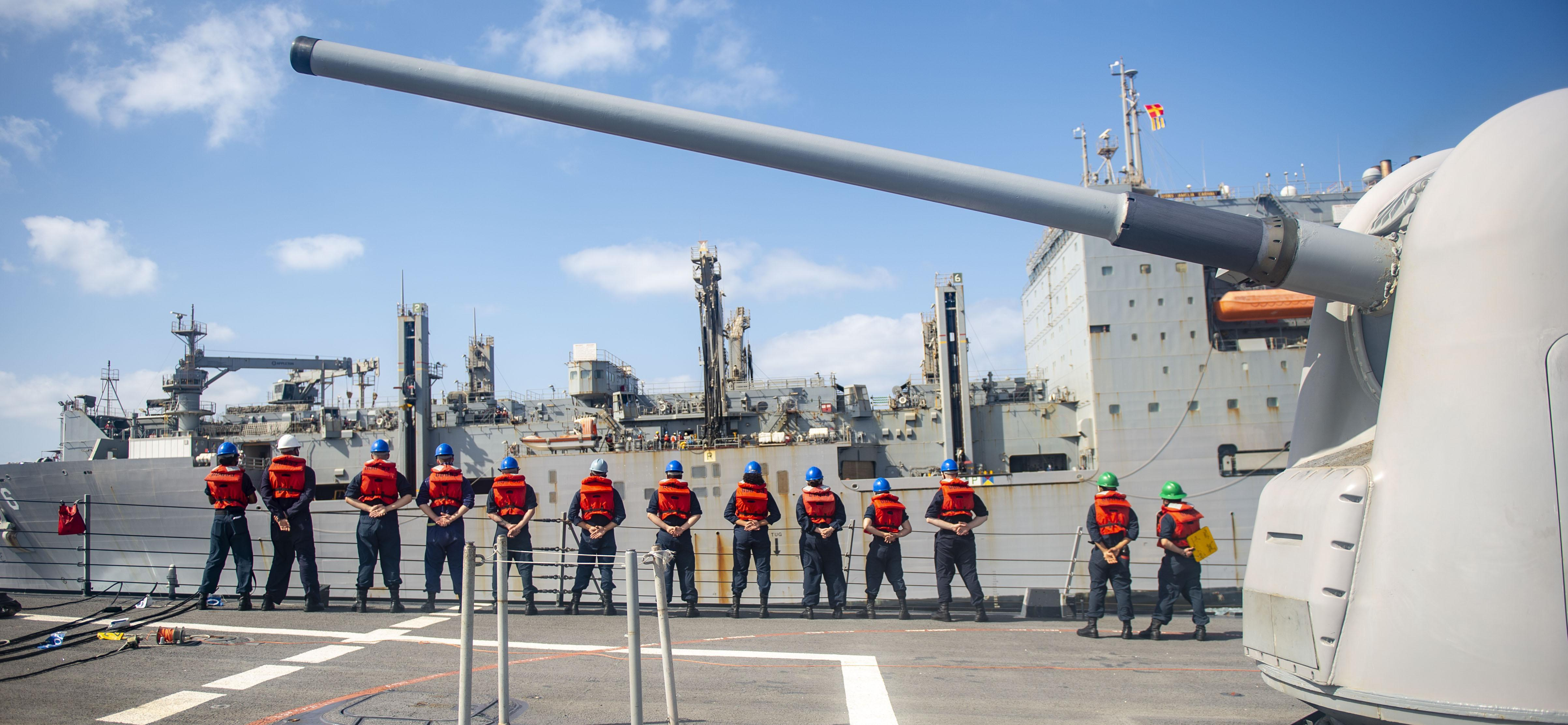 Sailors aboard USS John Paul Jones (DDG 53) stand in formation during a replenishment-at-sea with USNS Amelia Earhart (T-AKE 6) in the Indian Ocean.