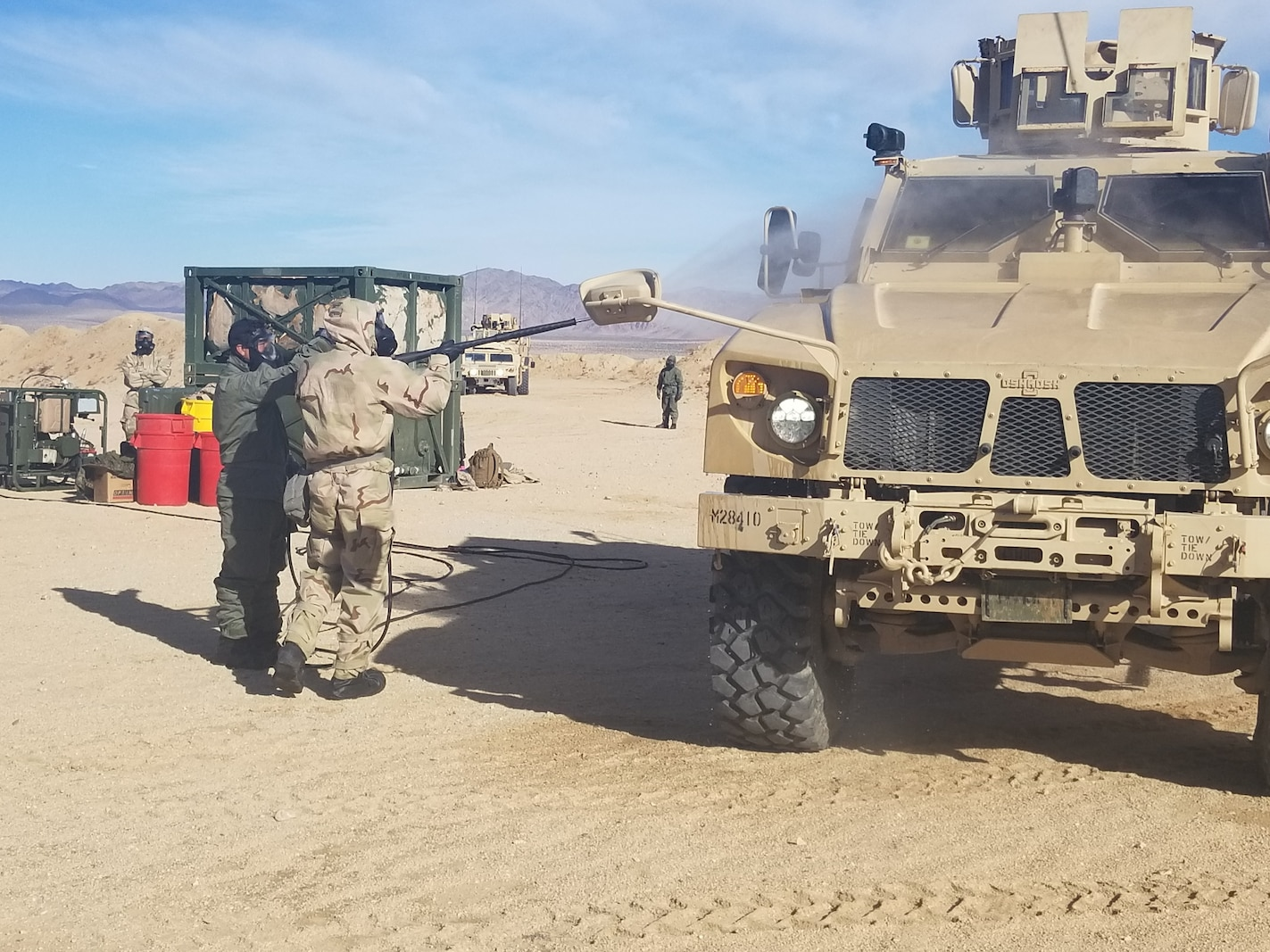 Marines with Headquarters Company, Combat Logistics Regiment 1, conduct a washdown of vehicles after a simulated CBRN attack during Exercise Steel Knight on December 11, 2019.