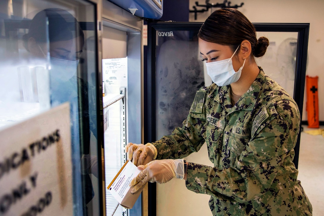 A Navy seaman wearing a face mask and gloves prepare vaccines.