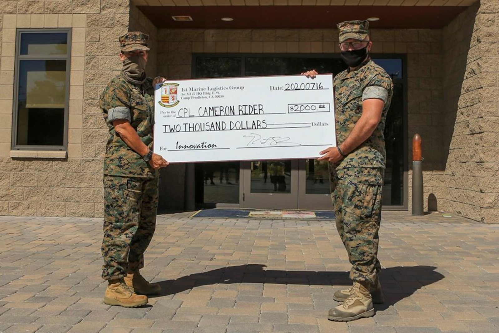Commanding General of 1st Marine Logistics Group Brig. Gen. Bobbi Shea awards $2000 to the winner of 1st MLG Innovation Award, Cpl. Cameron Rider, a radio operator with Combat Logistics Regiment 1, for his design and fabrication of a vehicle-mounted antenna on Camp Pendleton, California, July 16, 2020.
