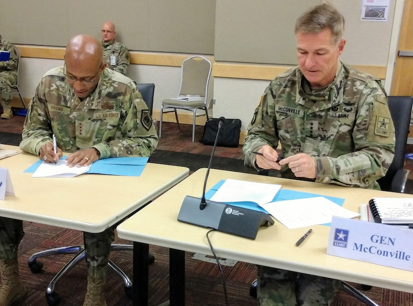 Two military officers sign agreements.