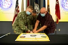 Joint Task Force Civil Support Commander Maj. Gen. Jeffrey Van, center, cuts a cake with Navy Hospital Corpsman Tyler Arentzen and Paul Marcinko, the oldest and youngest members respectively, during the command's 21st anniversary celebration.