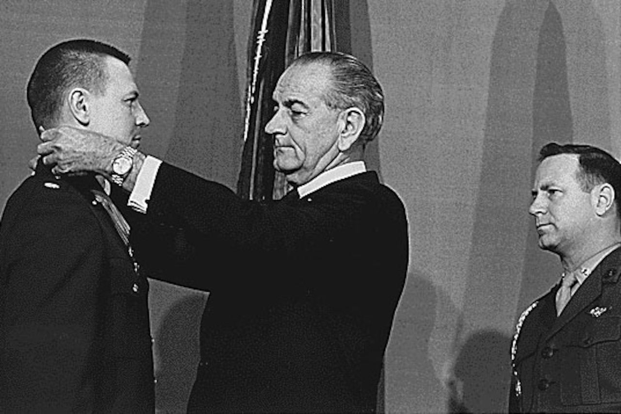 A man puts a medal around another man's neck as a third man watches.