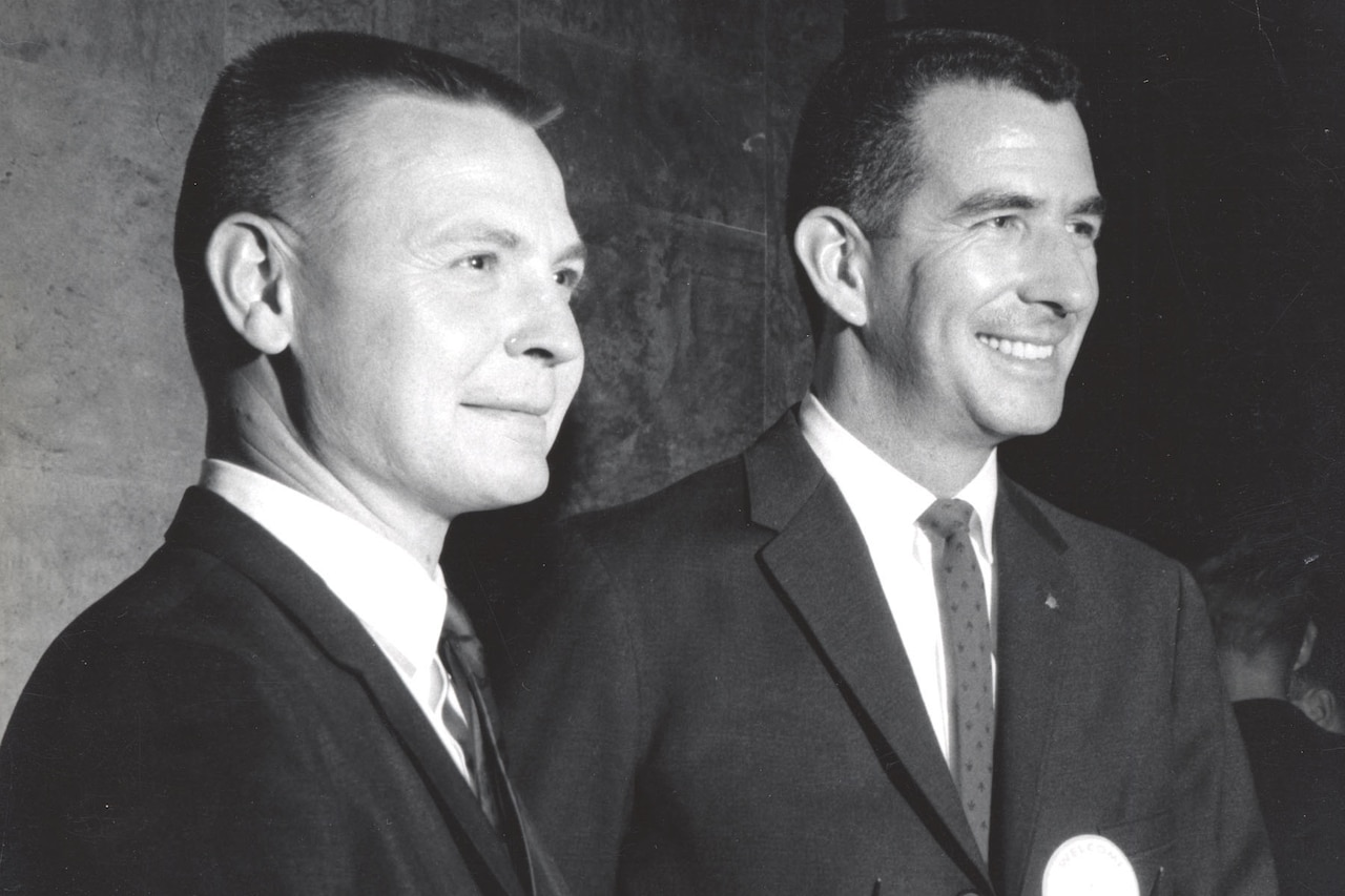 Two men in suits smile.