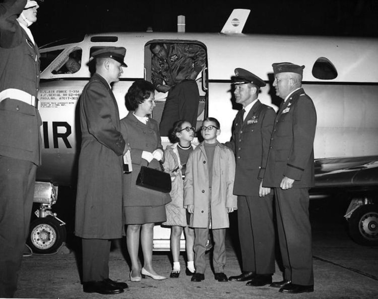 Two military men greet a family of four outside the door of a small airplane.