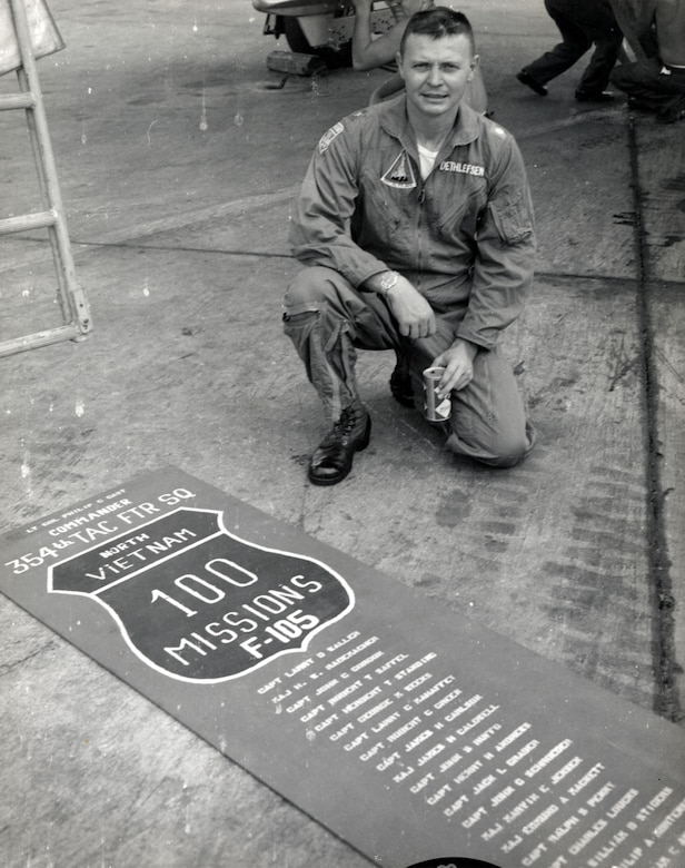 A man kneels on the ground beside a poster noting 100 missions over North Vietnam.
