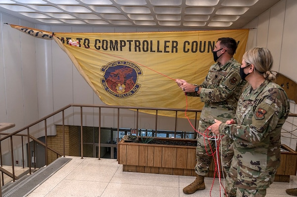 Brig. Gen. Caroline Miller, 502d Air Base Wing and Joint Base San Antonio commander, right, visited the Dragons on Sept. 30 to congratulate the budget analysis team and to unfurl the unit banner—symbolically celebrating the 502ndComptroller Squadron consolidation efforts at JBSA-Lackland and the reopening of customer lobbies at all JBSA locations.