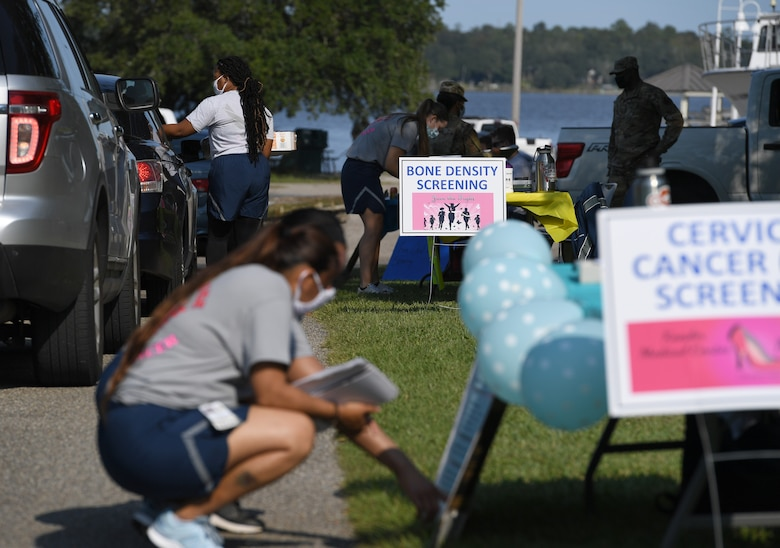 Members of the 81st Medical Group assist attendess during the 81st MDG Drive-Through Health Expo at the Marina at Keesler Air Force Base, Mississippi, October 2, 2020. The 81st MDG hosted the drive-through event, which included scheduling appointments for mammograms and multiple types of cancer and chronic diseases in honor of Breast Cancer Awareness Month. (U.S. Air Force photo by Kemberly Groue)