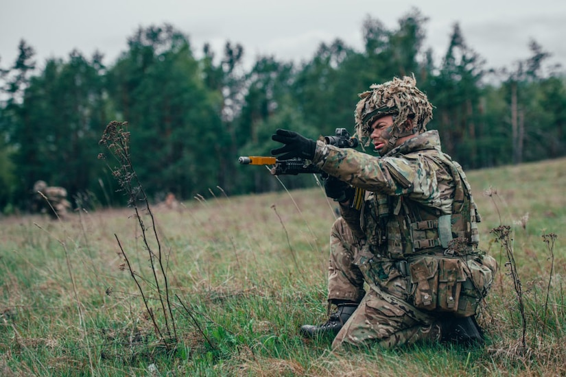 A soldier wearing camouflage gear sits on the ground in a field to aim his weapon.