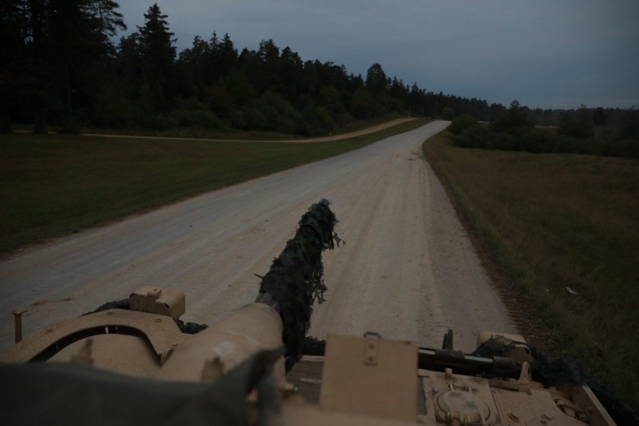 The view of a road and trees from inside a military vehicle.