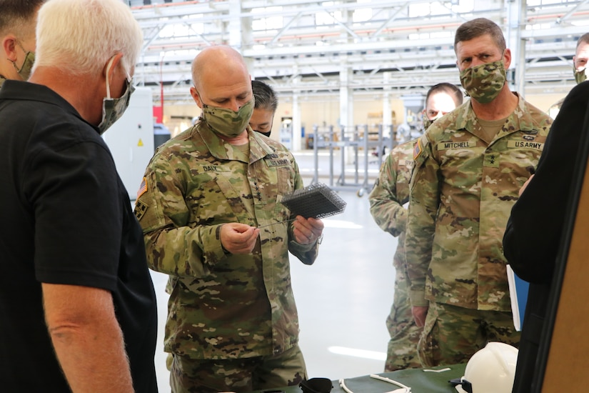 A man examines a long, thin piece of plastic as other men stand nearby; all are wearing face masks.