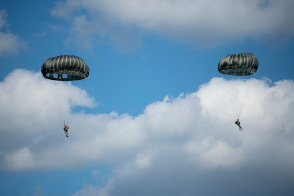 Two military personnel are parachuting.