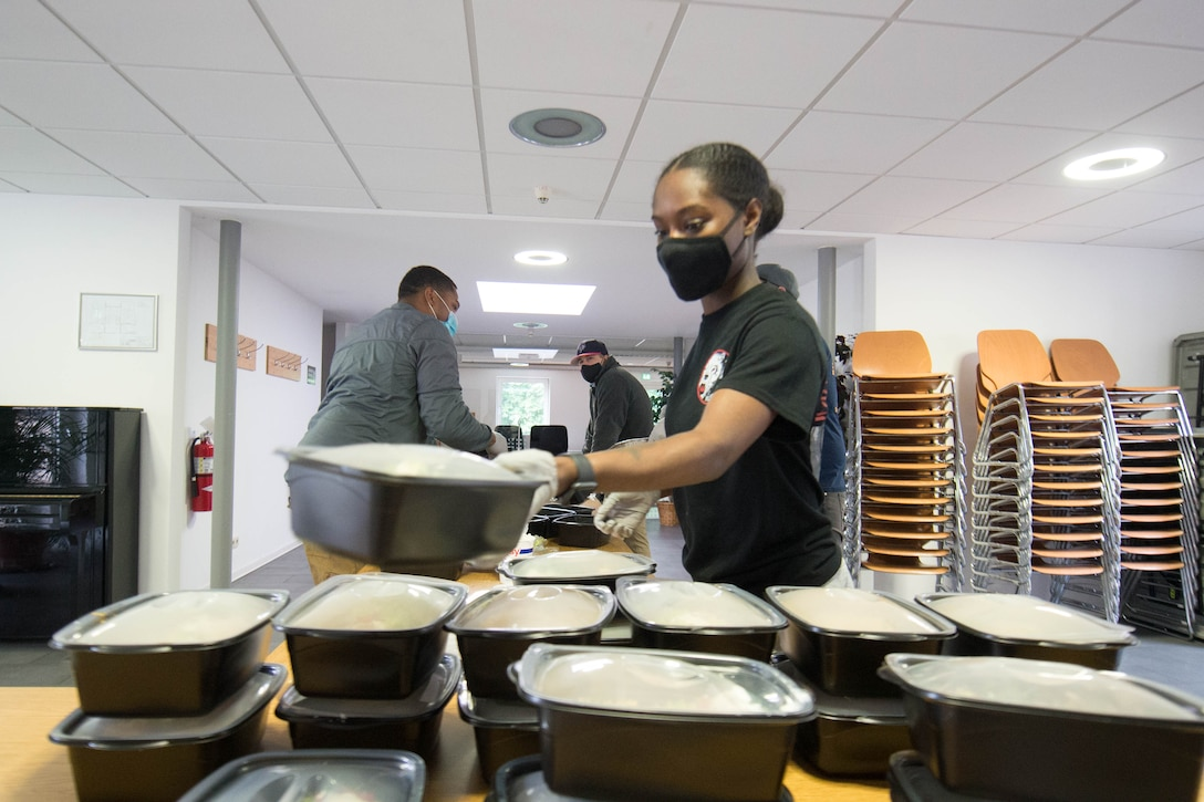 Photograph of a volunteer stacking meals that are ready for delivery.