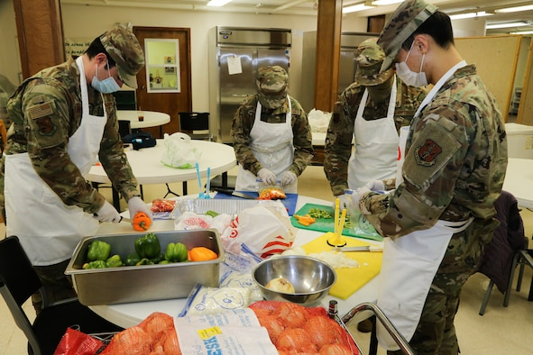 From left to right, Alaska Air National Guard Tech Sgt. Brayden Van Bevera, Airman 1st Class Fionna Kelty, Tech Sgt. Allen Wilson and Senior Airman Alex Choi, all members of the 176th Force Support Flight Sustainment Services, cut fresh produce at the Five Loaves, Two Fish Kitchen in Wasilla, Alaska, Sept. 25, 2020. The Airmen have been volunteering at the kitchen since mid-August, preparing an average of 150 meals per week for non-profit organizations.