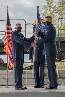 Col. Kenneth M. Lute, commander of the 911th Mission Support Group, passes the guidon during an assumption of command ceremony to Maj. Erik Hofmeyer, commander of the 32nd Aerial Port Squadron, at the Pittsburgh International Airport Air Reserve Station, Pennsylvania, Oct. 3. 2020.