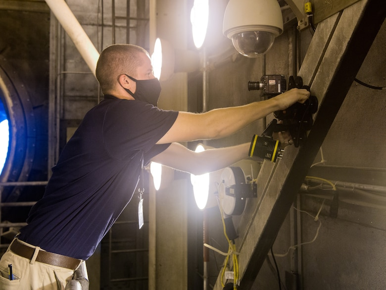 Seth Beaman, a Naval Air Systems Command aeropropulsion test analyst, sets up a high-speed camera, Sept. 1, 2020, in the sea-level test cell SL-1 at Arnold Air Force Base, Tenn. The camera, combined with software, allows for the observation and measurement of vibrations. Beaman is studying the potential for its use as an analysis tool for engine testing. (U.S. Air Force photo by Jill Pickett)