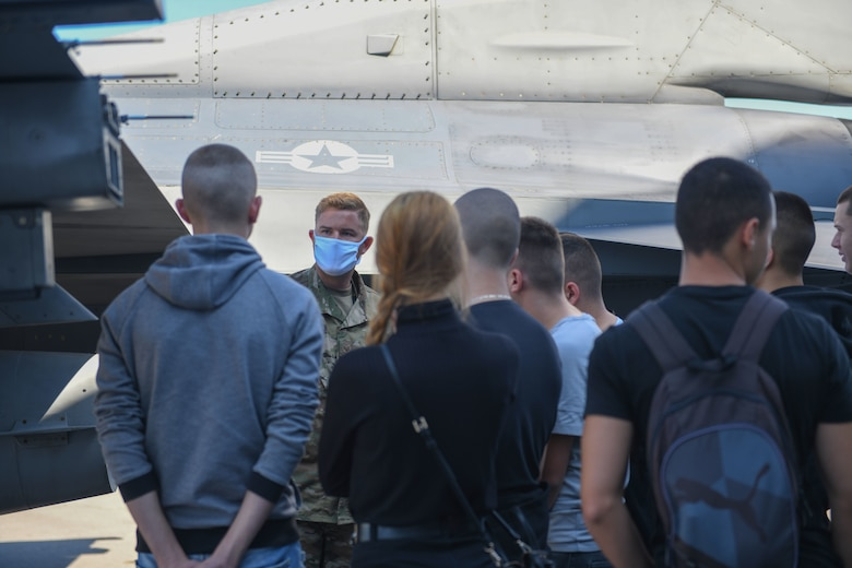 U.S. Air Force Staff Sgt. Richard Rygiel, 31st Aircraft Maintenance Squadron crew chief, speaks to students from First English Language School, Sofia, Bulgaria, during NATO enhanced Air Policing Oct. 2, 2020, at Graf Ignatievo Air Base, Bulgaria. The First English Language School was founded in 1958 as a high school for education in English language. During their visit, the students learned about various parts of a U.S. Air Force F-16 Fighting Falcon, and had the opportunity to sit in the cockpit of the aircraft. (U.S. Air Force photo by Airman 1st Class Ericka A. Woolever)