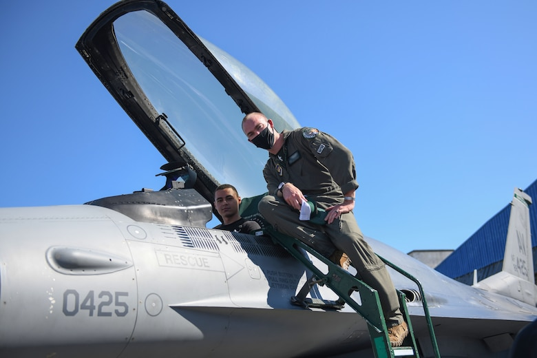A U.S. Air Force pilot from the 555th Fighter Squadron, Aviano Air Base, Italy, and a student from First English Language School, Sofia, Bulgaria, pose for a photo, Oct. 2, 2020, at Graf Ignatievo Air Base, Bulgaria. The students met with both a pilot and a crew chief for about 25 minutes and discussed the various parts of a U.S. Air Force F-16 Fighting Falcon. During their visit, the students had the opportunity to practice the English language while discussing the various parts of the aircraft. (U.S. Air Force photo by Airman 1st Class Ericka A. Woolever)