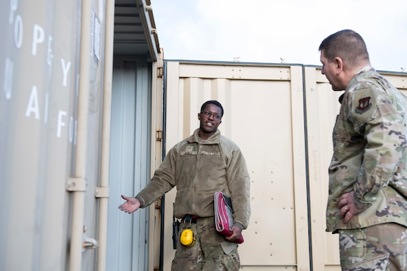 U.S. Air Force Senior Airman Andre Mobley, left, 420th Munitions Squadron stockpile technician, shares with Col. Kurt Wendt, right, 501st Combat Support Wing commander, information about the necessary cleaning and qualifications for explosive International Standards Organization (ISO) shipping containers, during a visit to RAF Welford, England, Oct. 1, 2020. Wendt visited 420th MUNS to meet with the Airmen and to learn more about their new mission capabilities. (U.S. Air Force photo by Senior Airman Jennifer Zima)