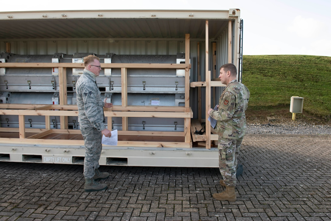 U.S. Air Force Senior Airman Ian Fike, left, 420th Munitions Squadron conventional maintenance crew chief, shows Col. Kurt Wendt, right, 501st Combat Support Wing commander, regulations and instructions to build wooden blocking and bracing to secure munitions during shipment, during a visit to RAF Welford, England, Oct. 1, 2020. Wendt visited 420th MUNS to meet with the Airmen and to learn more about their new mission capabilities. (U.S. Air Force photo by Senior Airman Jennifer Zima)