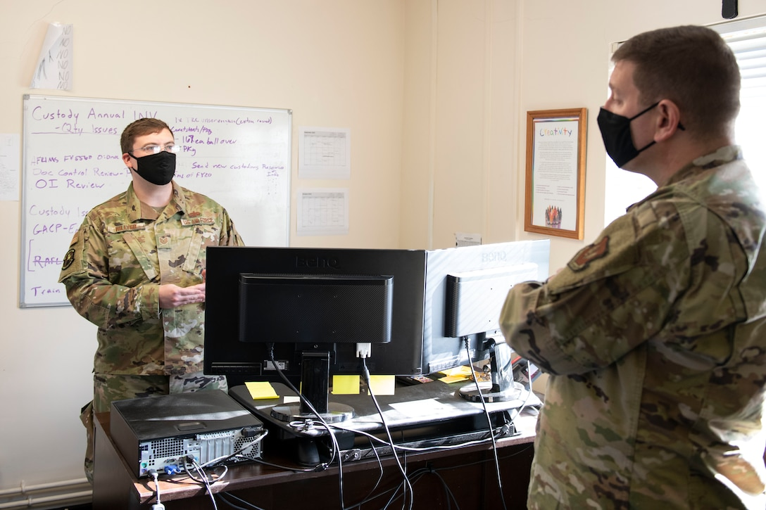 U.S. Air Force Tech. Sgt. Jacob Hillyer, left, 420th MUNS noncommissioned officer in charge of munitions operations, shares with Col. Kurt Wendt, right, 501st Combat Support Wing commander, information about the new munitions stockpile inventory system, the Theater Integrated Combat Munitions Systems (TICMS), during a visit to RAF Welford, England, Oct. 1, 2020. Wendt visited 420th MUNS to meet with the Airmen and to learn more about their new mission capabilities. (U.S. Air Force photo by Senior Airman Jennifer Zima)