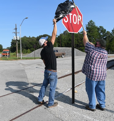 Laborers Danny Smartt, left, and Kelvin Sweeton uncover one of four stop signs installed at an intersection near the J-4 Rocket Motor Test Facility at Arnold Air Force Base, Tenn., Sept. 11, 2020. The signs were uncovered after craftsmen were notified of their installation during toolbox meetings. (U.S. Air Force photo by Jill Pickett)