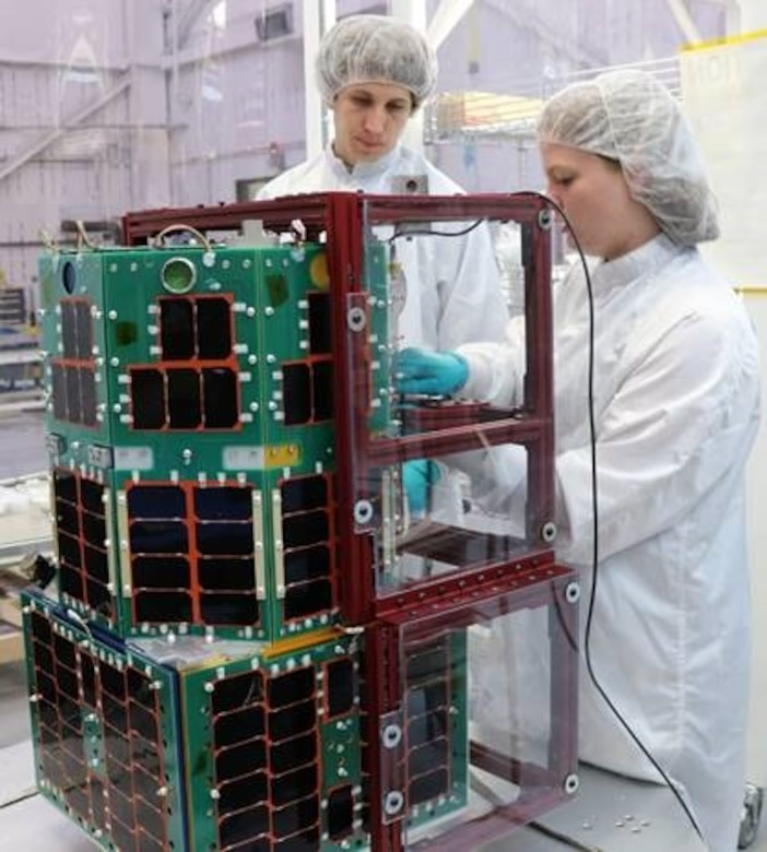 Two people assemble a satellite