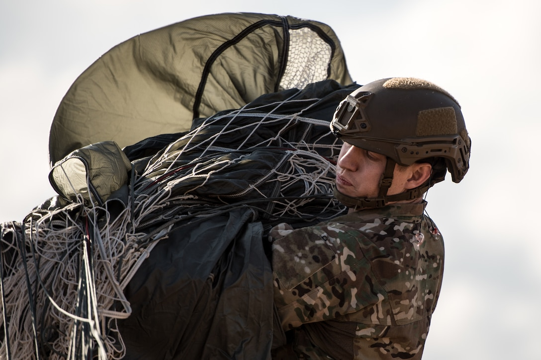 Photo of Airman packing a used parachute