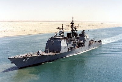 A Navy ship moves from right to left in blue water with sand of the desert behind it.