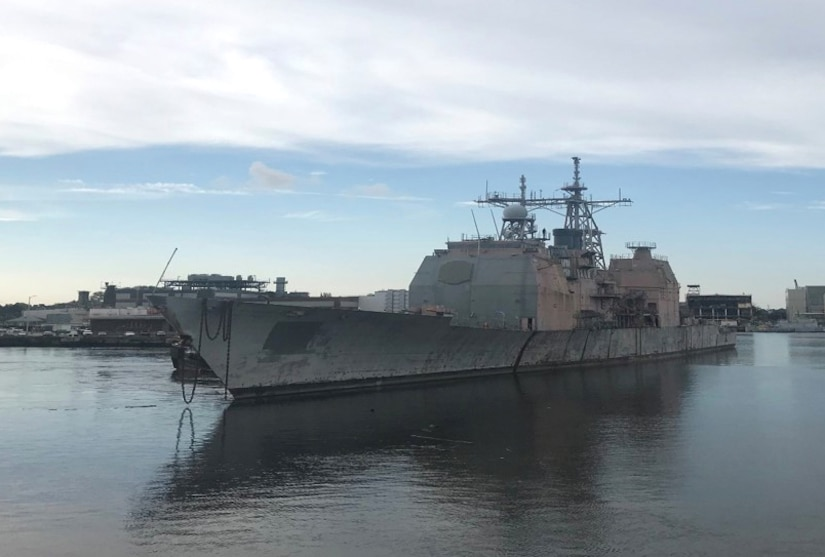 The ex-USS Ticonderoga (CG47) sits in an industrial dock area showing her age.