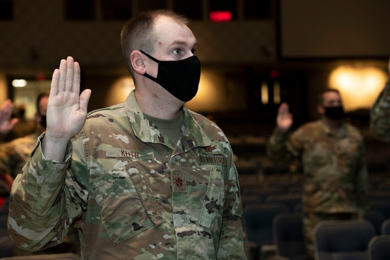 Air Force officers, assigned to Air University, raise their right hand and recite the Oath of Office during a ceremonial swear-in in Polifka Auditorium.