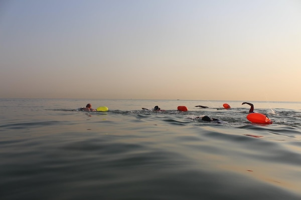 Eric Reich, left, Defense Logistics Agency Disposition Services' operations supervisor and site lead at Camp Arifjan, leads the way against 30 competitors during a Sept. 18 one kilometer open water swim in the Persian Gulf at Abu Halifa Beach.