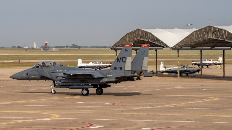 An F-15E Strike Eagle from the 389th Fighter Squadron taxis for takeoff at Vance AFB while student pilots start and taxi in the T-6 Texan II pilot trainer. (U.S. Air Force photo by Maj. Mark Calendine)